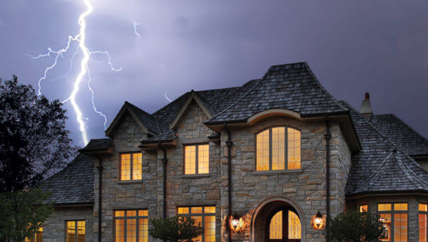 stone house at night with lightning in background sky