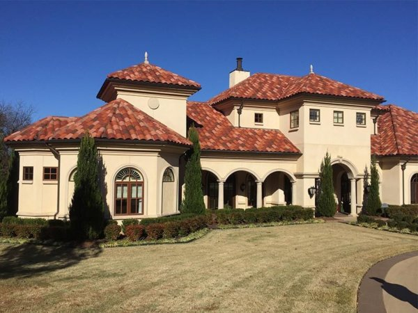 large brown two story home with tile roof