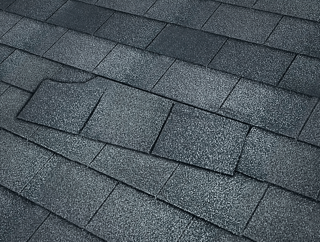 grey composite shingle roof torn out of place